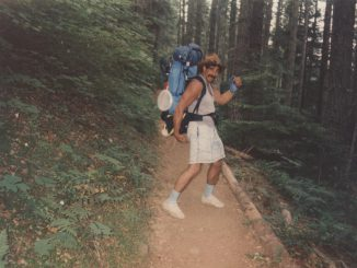 My dad standing on a trail doing a silly pose wearing a hiking backpack and funny hat and looking super fit.